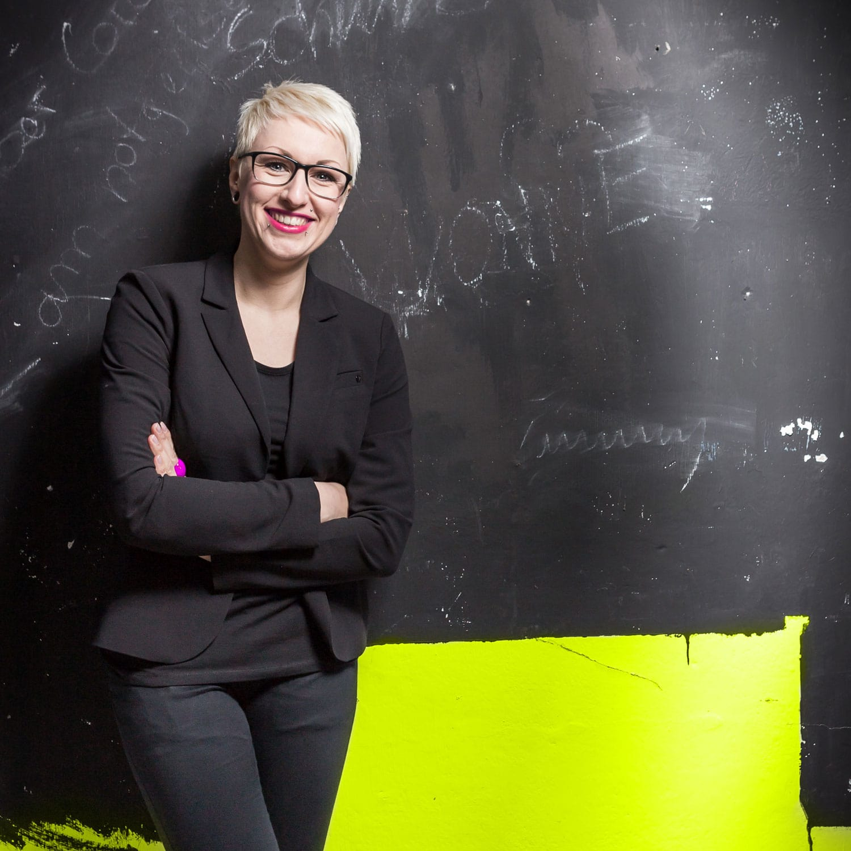 Lena stehend an schwarzer Wand im Business-Outfit, lachend