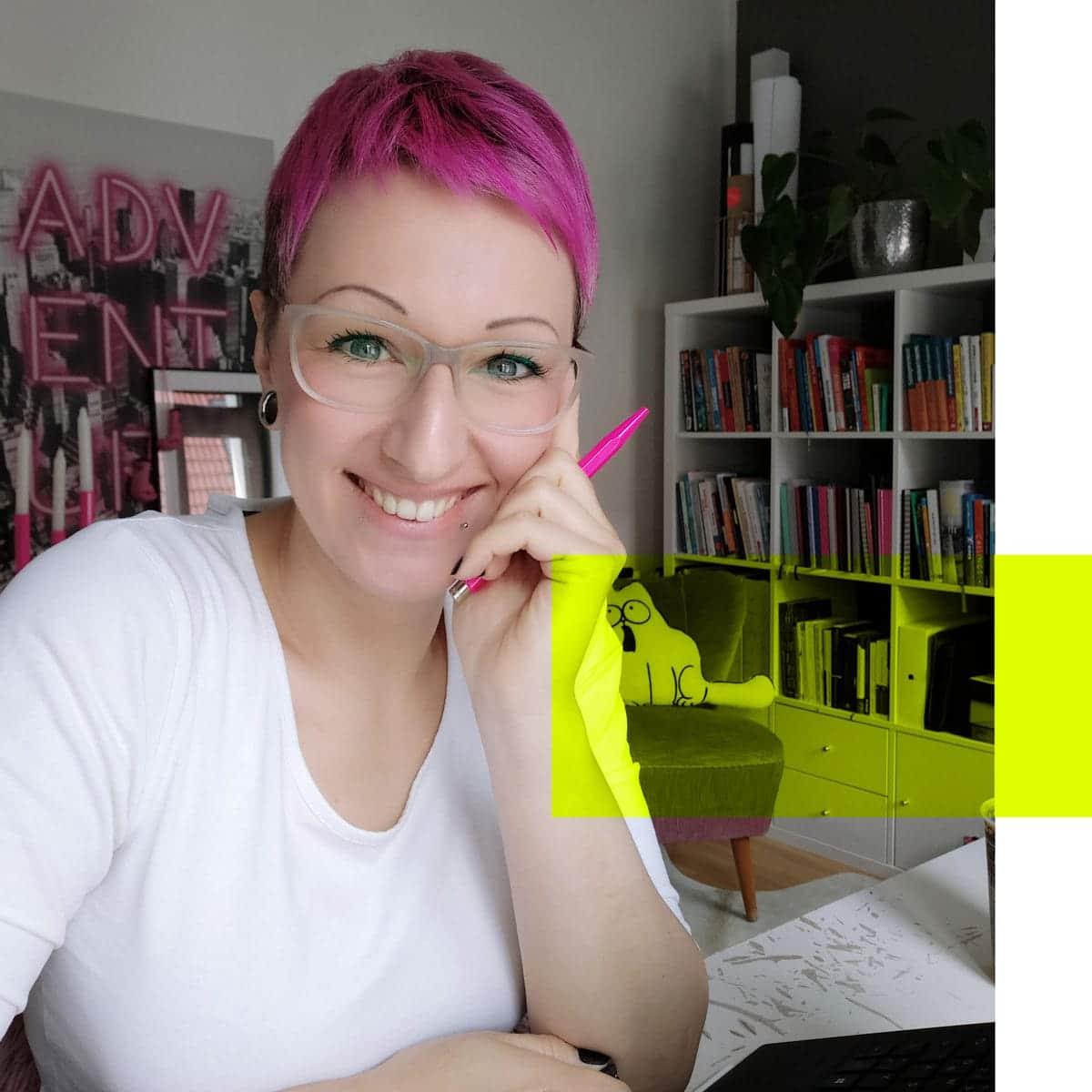 Lena sitzend am Schreibtisch, blickt lächelnd in die Kamera