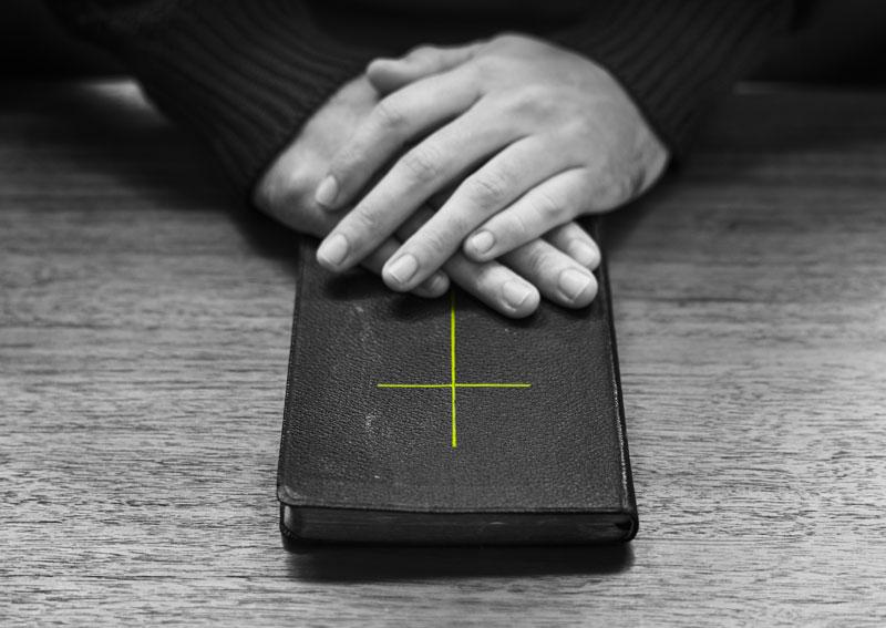 Schwarz-weiß Bild, Hände auf Bibel mit neongelbem Kreuz